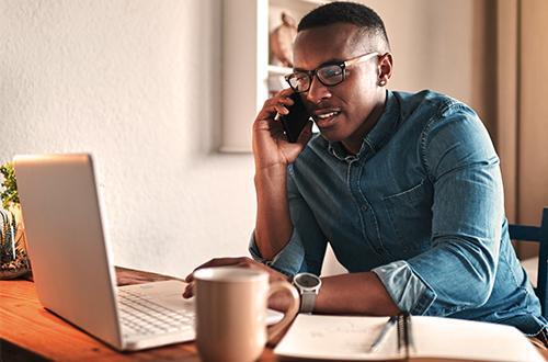 hombre en su teléfono y mirando su computadora portátil