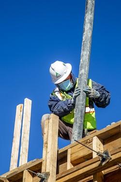Trabajador guiando manguera de vertido de hormigón