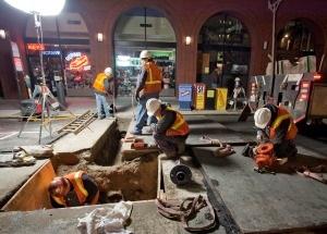 Tripulación nocturna haciendo reparaciones en la calle