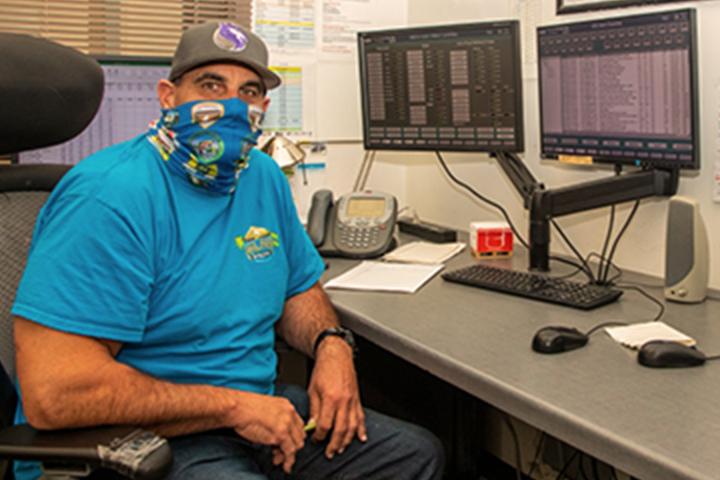 فني مقنع يجلس في محطة عمل الكمبيوتر
