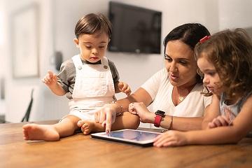 madre y sus dos hijos pequeños sentados a la mesa