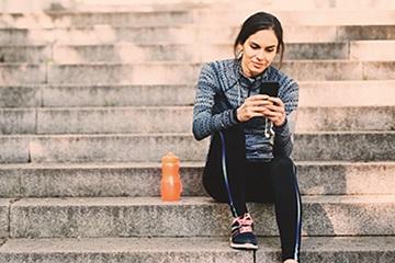 mujer sentada en los escalones y enviando mensajes de texto en su teléfono