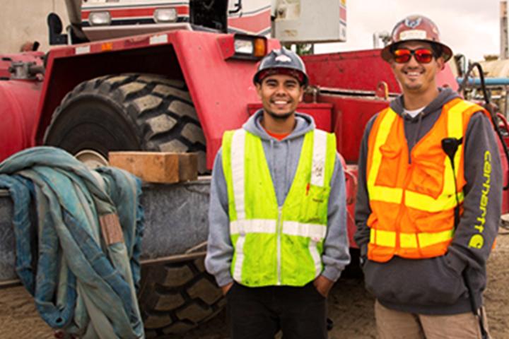 兩名工人肩並肩站在拖拉機前