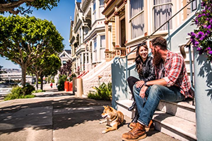 Hombre, mujer y su perro sentados en los escalones de la entrada del edificio.