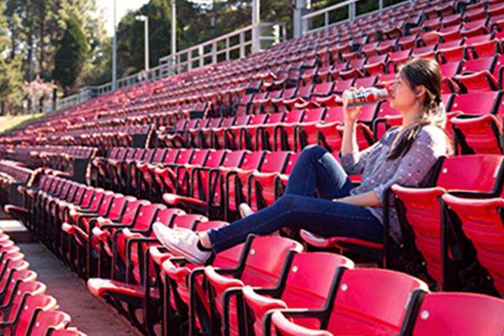 女人獨自一人坐在體育場座位上從瓶水喝