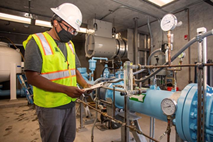 戴著面具的技術員檢查水泵