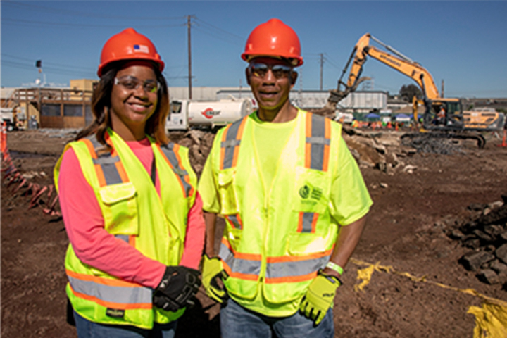 two construction workers standing shoulder to shoulder