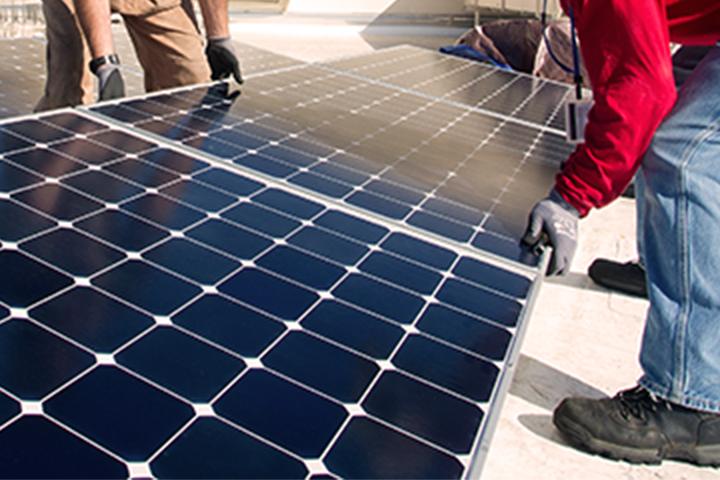 manos levantando un panel solar