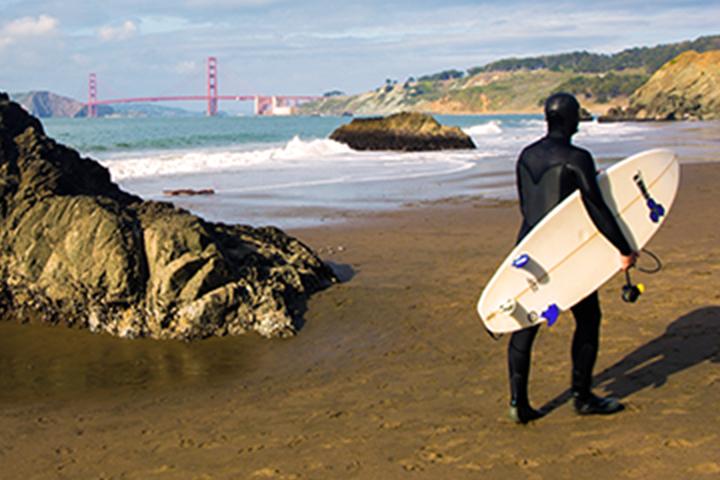 Surfista con tabla caminando en la playa de Baker
