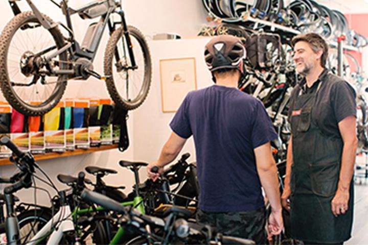 dos hombres hablando dentro de una tienda de bicicletas
