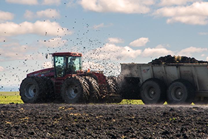 tractor esparcir fertilizante sobre un campo