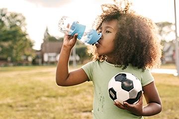 Niño de pelo rizado sosteniendo una pelota de fútbol y bebiendo de una botella de agua