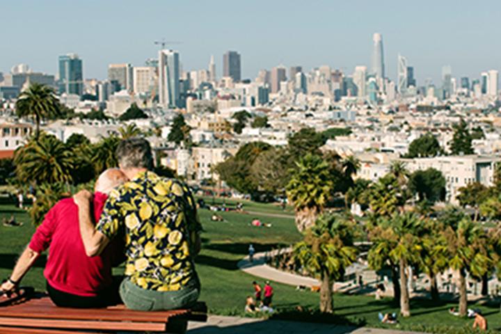 hai người đàn ông ngồi trên băng ghế nhìn ra Công viên Dolores