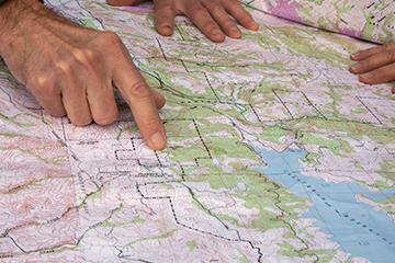mga kamay na nakaturo sa isang mapa