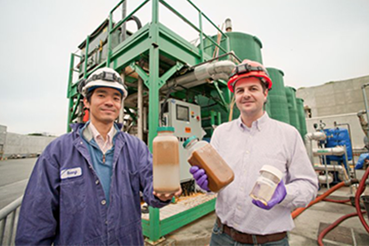 two men holding jars of waste grease