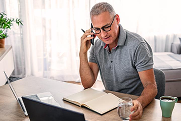 người đàn ông ở bàn làm việc và gọi điện thoại