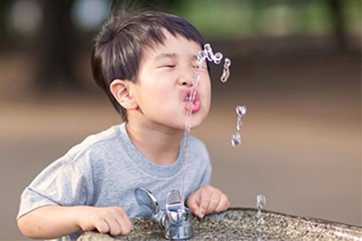 cậu bé uống nước từ đài phun nước