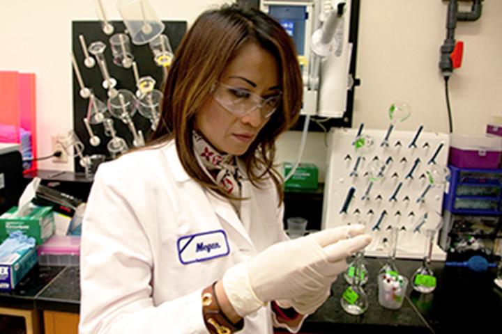 người phụ nữ mặc áo khoác phòng thí nghiệm xem xét biểu đồ
