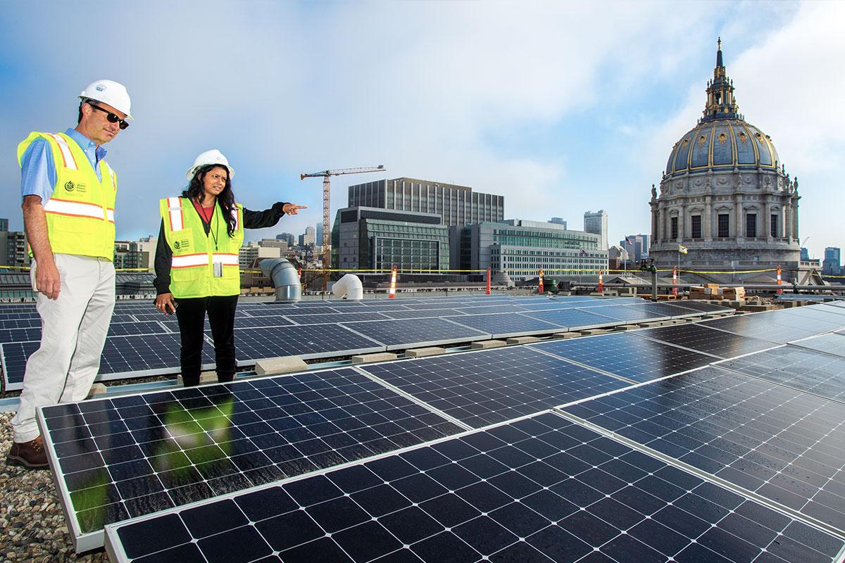 Dos empleados de la SFPUC miran los paneles solares en el Ayuntamiento.