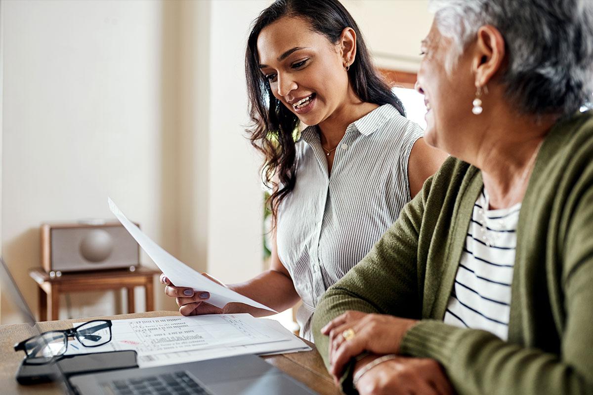 Dos mujeres miran un billete en una mesa.