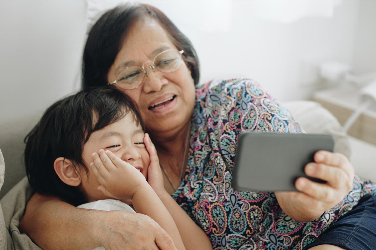 جدة وحفيدها ينظران إلى الهاتف معًا.