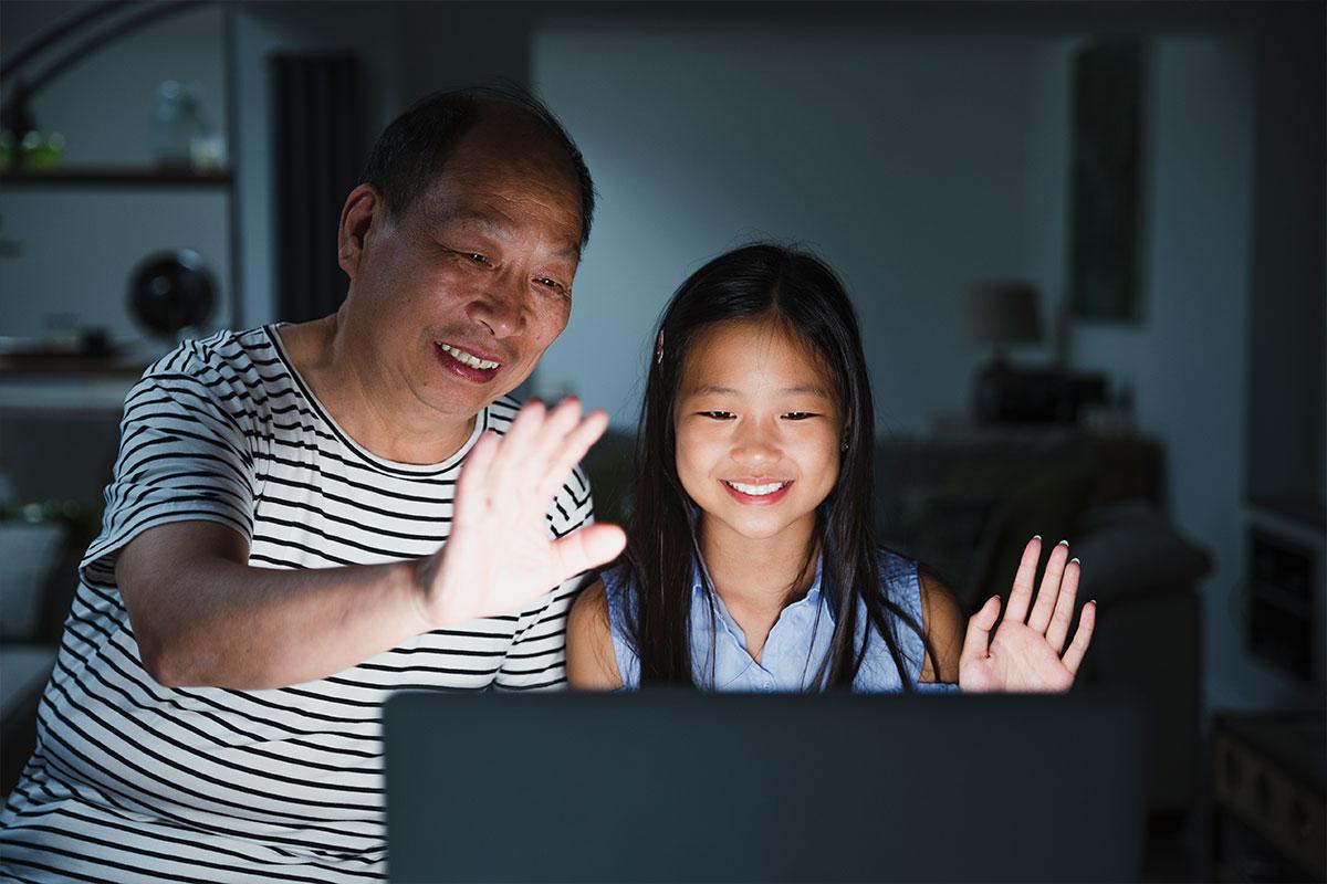 جد وحفيدة يبتسمان ويلوحان لشخص ما على شاشة الكمبيوتر في الليل