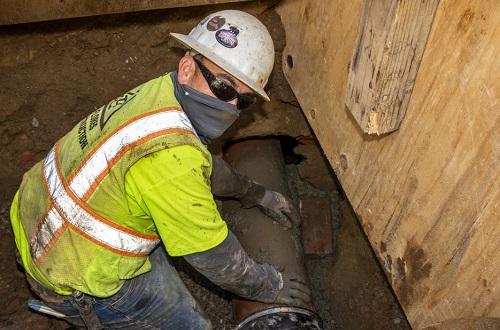 manggagawa sa isang trench na may hawak na isang sewer lateral