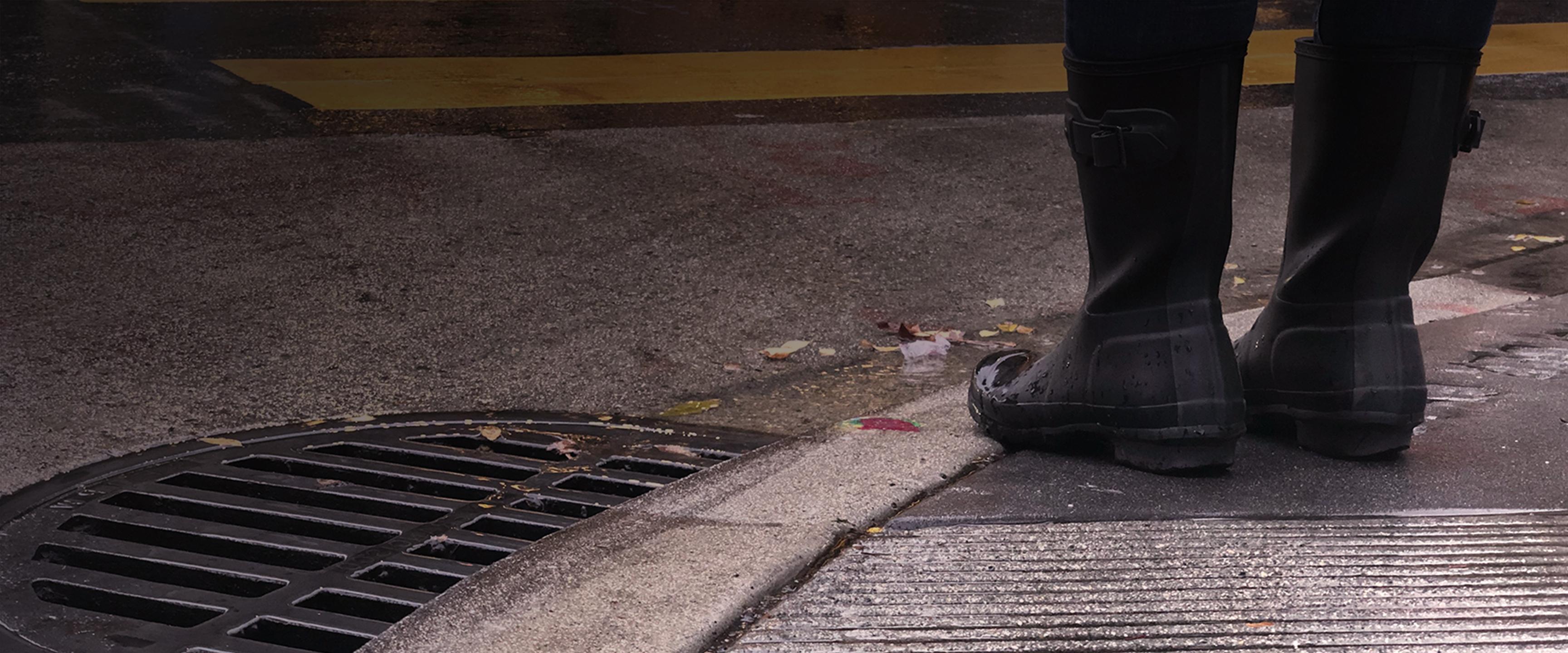ủng đi mưa đứng lề đường bên cống thoát nước