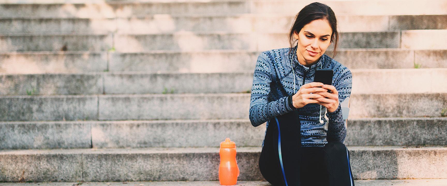 Женщина текстовых сообщений на своем смартфоне