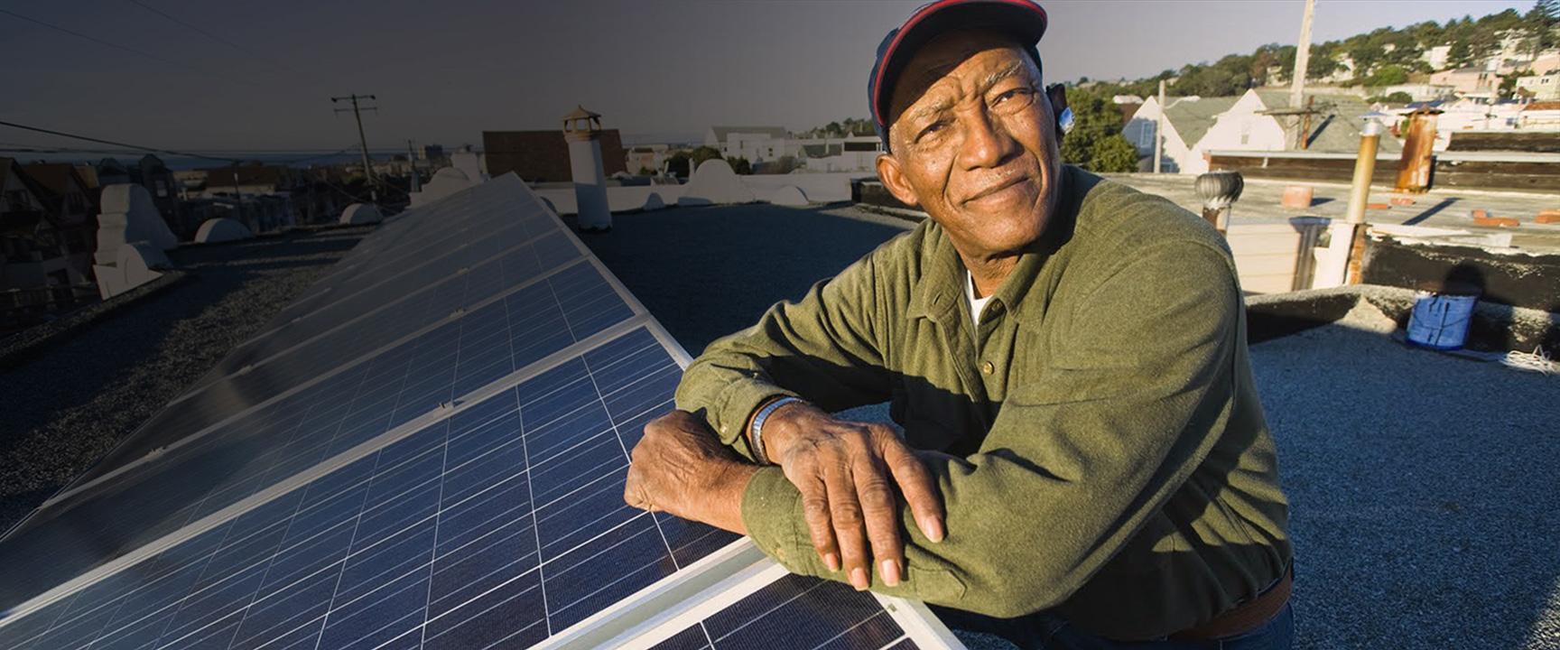 Hombre en el techo apoyado en paneles solares