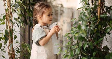 فتاة تحمل زجاجة رذاذ وتسقي نباتًا.